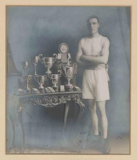 Photograph of a man with boxing trophies